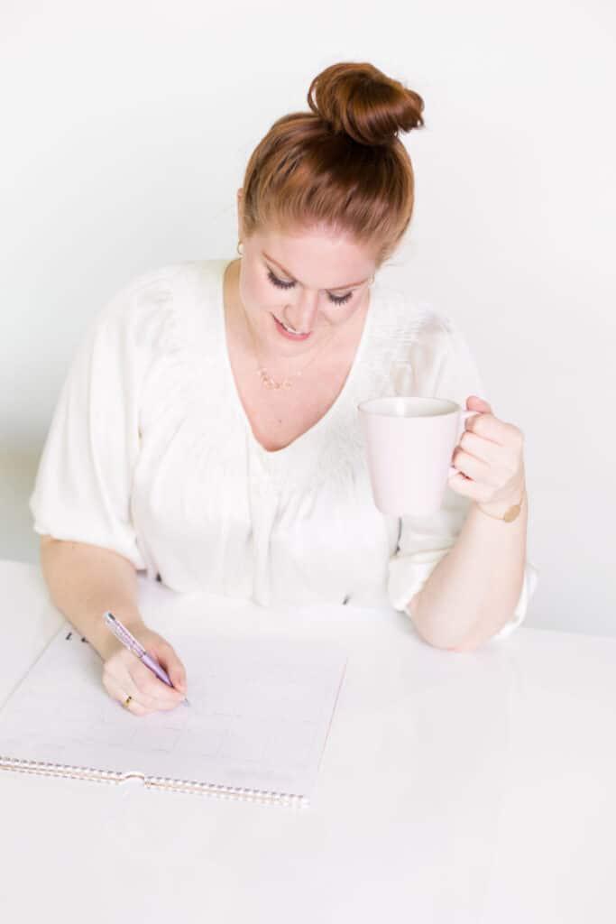 lady holding coffee mug sitting down to write
