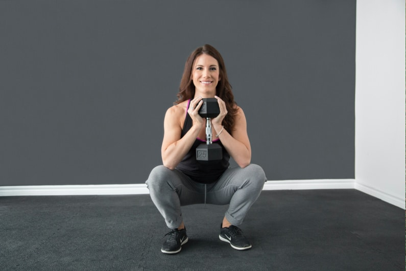 woman doing squats with a dumbbell and she is relieving stress