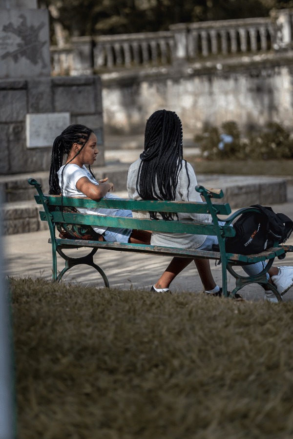 two ladies sitting on a park bench talking