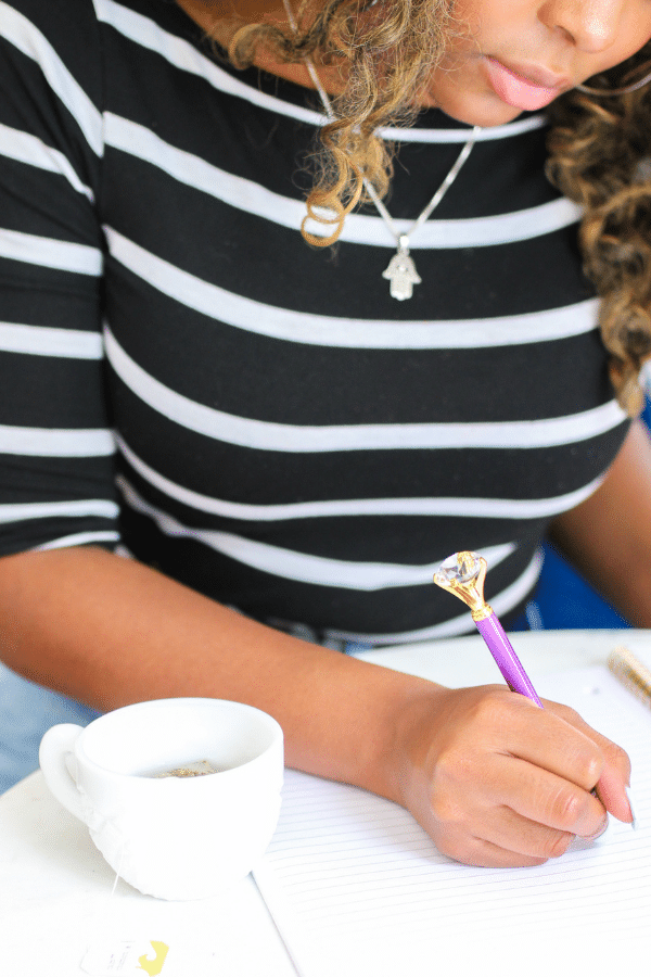 Woman writing notes in a notebook and she has a cup of hot tea on her desk.
