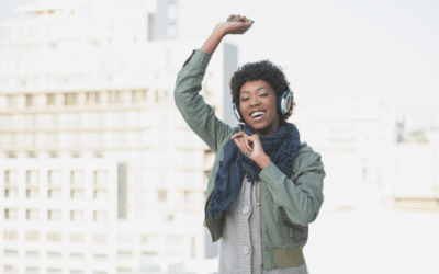 Woman listening to music on headphones as she dances in the street.