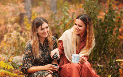 two ladies drinking warm beverages as they sit in a fall setting